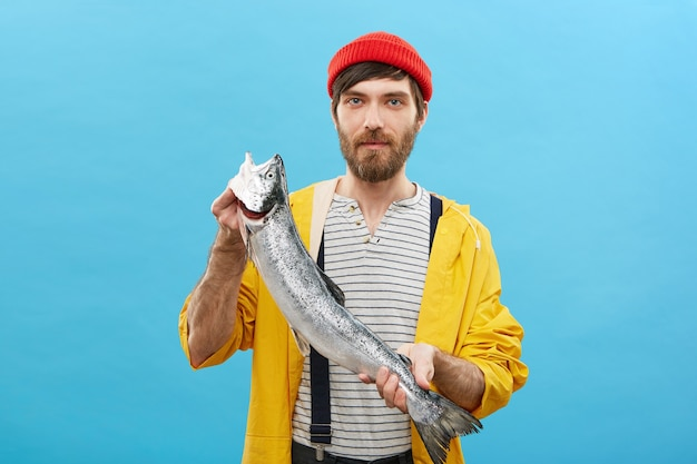 Portrait of bearded fisherman standing with huge fish