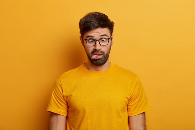 Portrait of bearded guy shows grimace, crosses eyes and sticks out tongue, plays around, going crazy, wears spectacles, everyday t shirt, poses against yellow wall. human face expressions