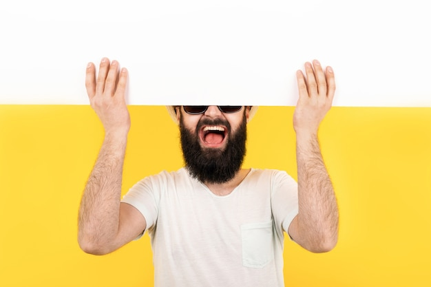 Portrait of a bearded guy in sunglasses, a man with an enthusiastic mood holding a white banner