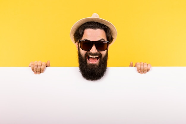 Portrait of a bearded guy in sunglasses and a panama hat, a man holds a white banner, summer billboard