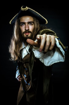 Portrait of bearded and hairy pirate pointing into the distance, shallow dof