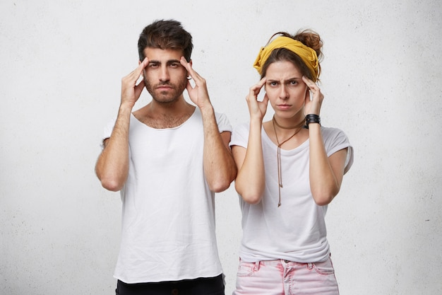 Portrait of bearded handsome man and beautiful woman with yellow headband on head trying to concentrate holding their hands on temples.
