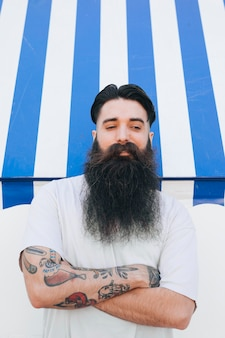 Portrait of a bearded handsome young man with tattoo on his hand