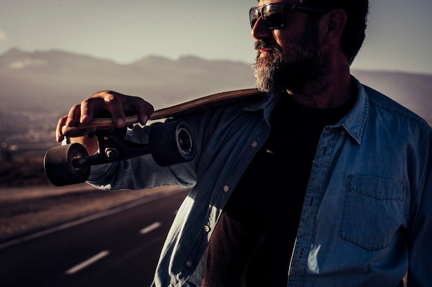 Portrait of bearded hipster mature man with long board table and asphalt road in background - concept of active and outdoor leisure activity for free people - dark shadow tones
