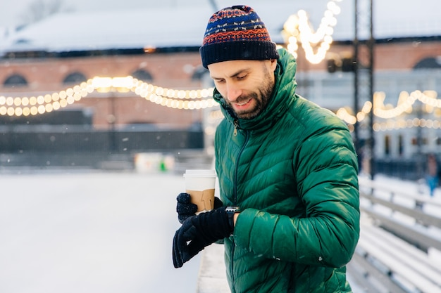 Portrait of bearded male dressed in warm clothes, looks at watch as waits for someone