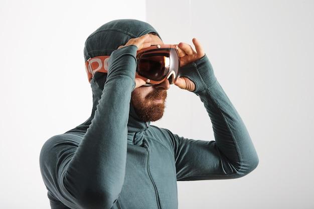 Il ritratto dell'atleta barbuto in tuta termica indossa occhiali da snowboard