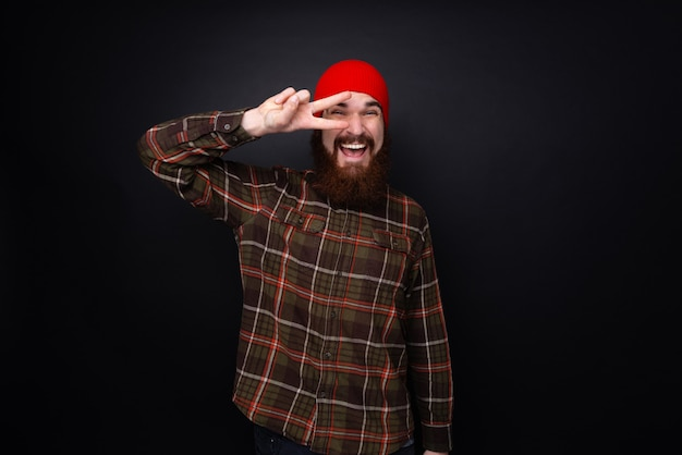 Portrait of bearded man doing pace sign  in front of eye over dark wall