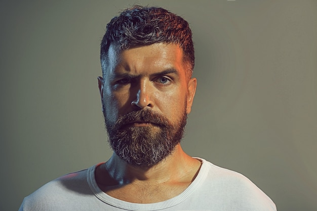 Portrait of bearded man face with stylish hairstyle in white shirt. confidence and success. sexy male model, serious face, fashionable hairstyle athletic bearded man. solid man with beard and mustache