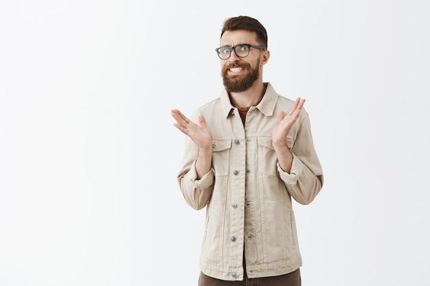 Ritratto di uomo barbuto in bicchieri in posa contro il muro bianco