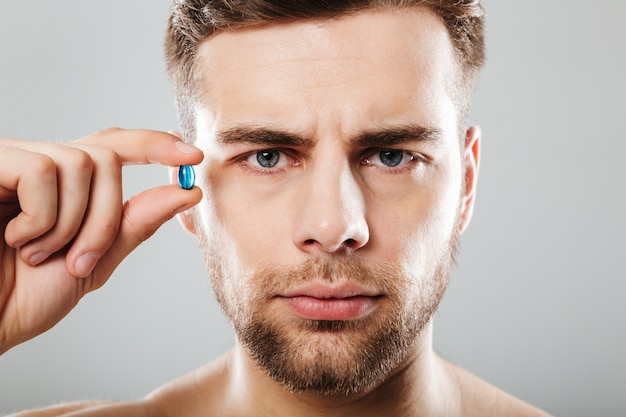 Portrait of a bearded man holding capsule at his face