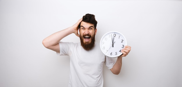 Portrait of a bearded man holding clock, delay and worried about discipline