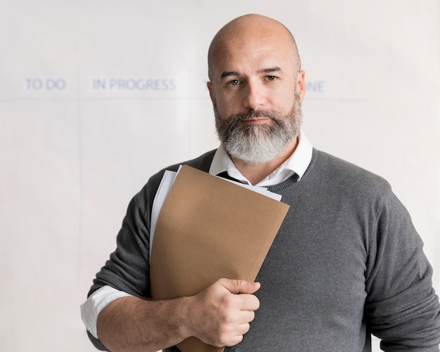 Portrait of bearded man holding documents