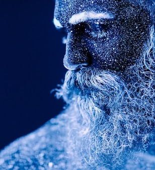 Portrait of a bearded man, the man is painted in ultraviolet powder.