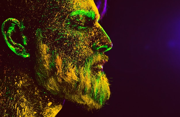 Portrait of a bearded man. man is painted in ultraviolet powder.