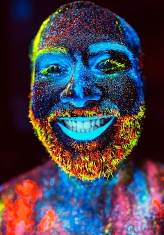 Portrait of a bearded man painted in fluorescent powder.