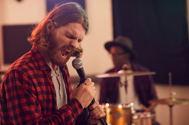 Portrait bearded man screaming to microphone while playing music during rehearsal