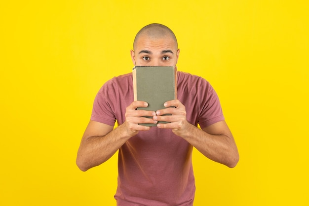 Portrait of a bearded man showing book cover  over yellow wall.
