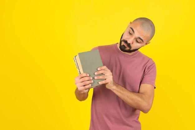 Ritratto di un uomo barbuto che mostra la copertina del libro sul muro giallo.