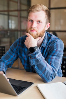 Portrait of bearded man sitting in front of laptop at workplace