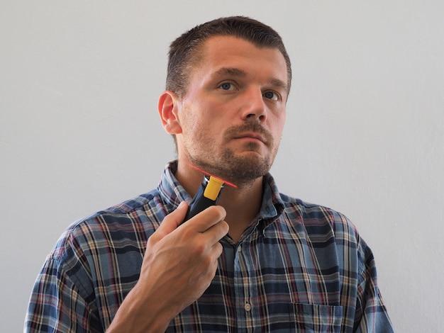 Портрет бородатого мужчины, подравнивающего бороду с лазерным красным уровнем. брить бороду.