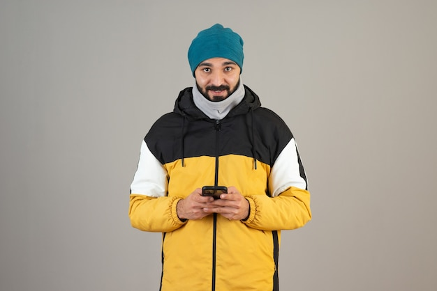 Portrait of bearded man in warm clothes standing and holding his mobile phone against gray wall .