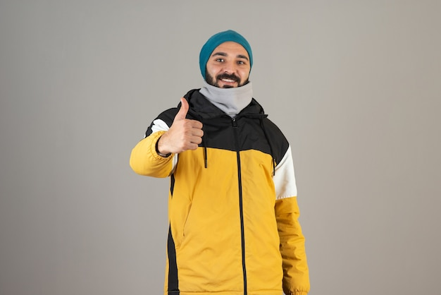Portrait of bearded man in warm clothes standing and showing thumb up .