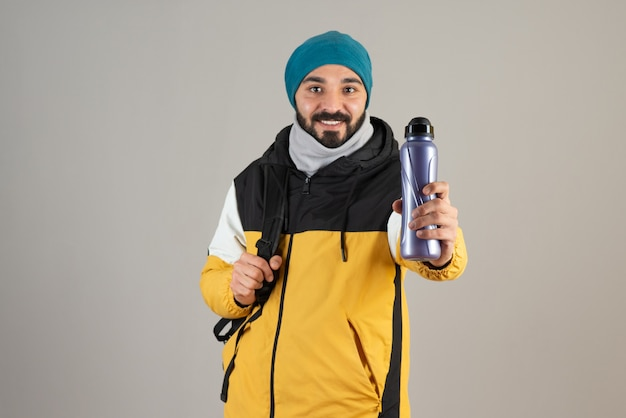 Portrait of bearded man in warm hat standing and holding water bottle against gray wall .