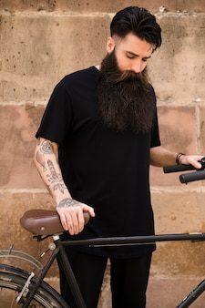 Portrait of a bearded man with bicycle standing in front of wall