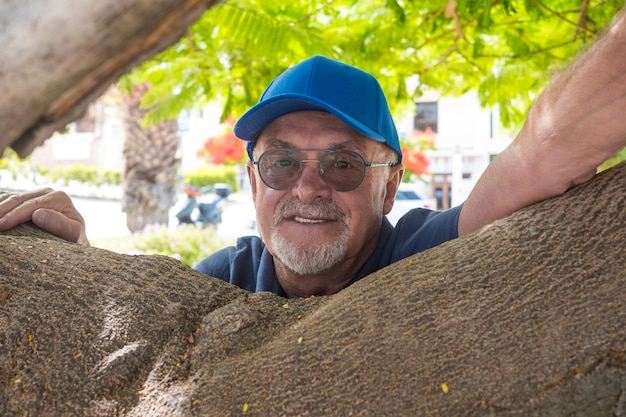 Portrait of bearded man with  glasses and cap leaning against tree branches under shadow of plants looking at camera. active senior retirement concept