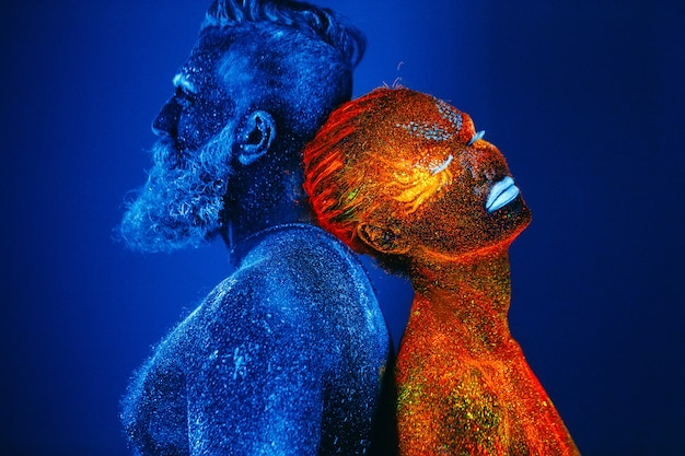 Portrait of a bearded man and woman painted in ultraviolet powder.