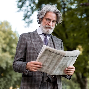 Portrait of bearded mature male reading newspaper