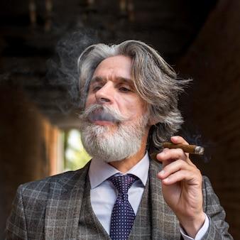 Portrait of bearded mature male smoking