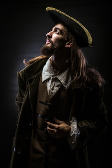 Portrait of a bearded pirate on black background