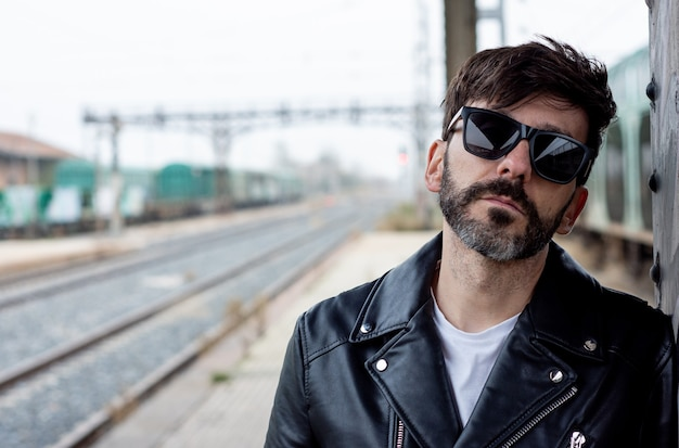 Portrait of a bearded rocker with sunglasses on an abandoned train station