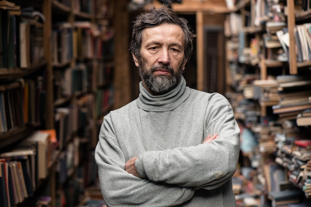 Portrait of bearded sad authentic senior man looking at camera in library