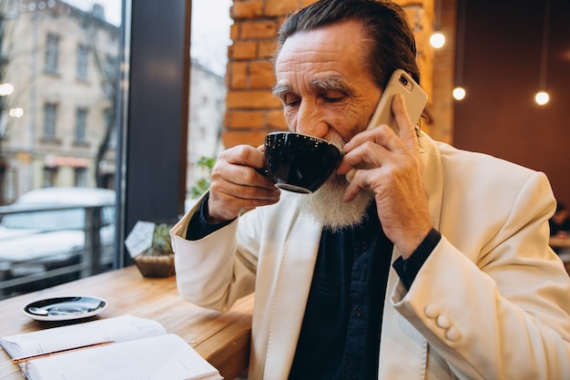 Portrait of a bearded senior man drinking coffee and using smart phone in cafe. portrait of happy grey bearded man sitting in cafe.