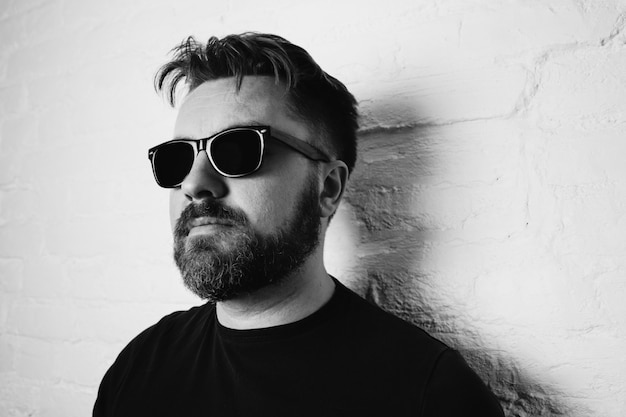 Portrait of a bearded serious man in sunglasses.