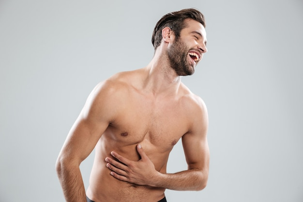 Portrait of a bearded shirtless man doubling up with laughter