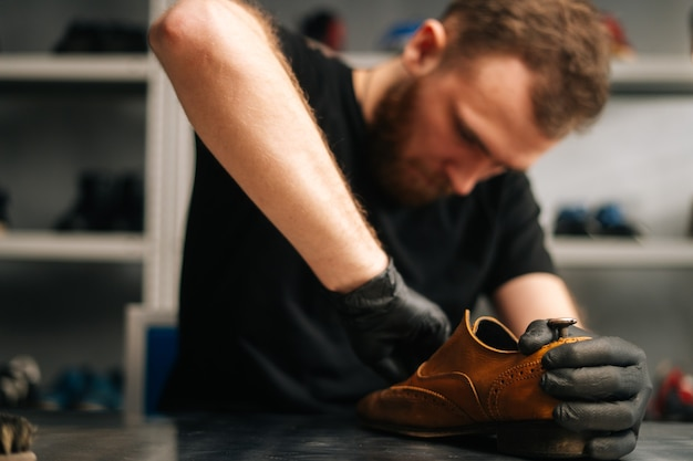 Portrait of bearded shoemaker cleaning old leather shoes for later restoration closeup