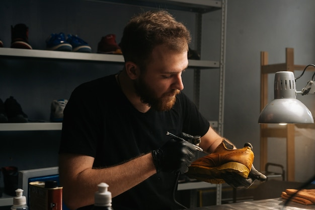 Portrait of bearded shoemaker wearing black gloves spraying paint of light brown leather shoes closeup