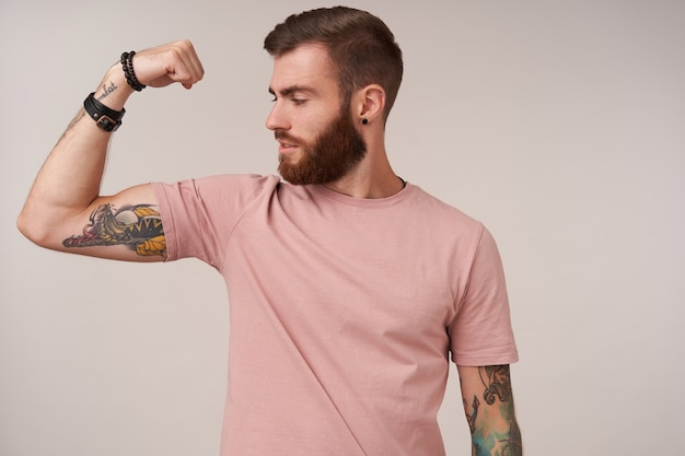 Portrait of bearded tattooed male having trendy haircut demonstrating his strong biceps, looking proudly on his raised hand, standing on white