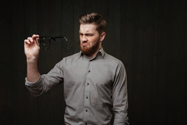 Portrait of a bearded unsatisfied disgusted man in shirt looking at eyeglasses isolated on the black wooden surface