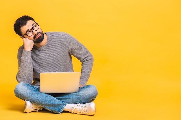 Portrait of a bearded young man in casual holding laptop computer while sitting on a floor isolated over yellow background. copyspace for text.