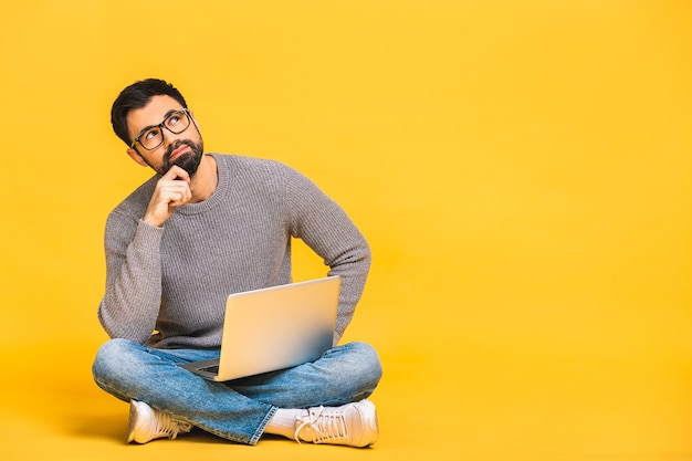 Portrait of a bearded young man in casual holding laptop computer while sitting on a floor isolated over yellow background