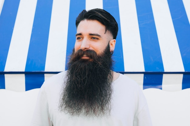 Portrait of a bearded young man standing in front of awning