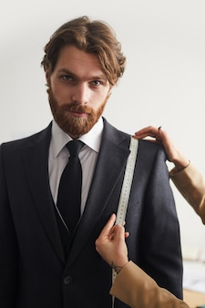 Portrait of bearded young man standing in suit while tailor measuring its length with tape measure