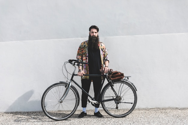 Portrait of a bearded young man standing with bicycle against wall