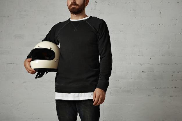 Ritratto di un giovane barbuto in felpa di cotone vuoto senza etichetta che tiene un casco da motociclista bianco isolato su bianco