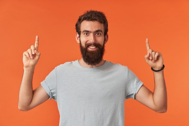 Portrait of bearded young man with brown eyes in white t-shirt is pointing fingers up, looking at you and up emotion happy glad and confident standing