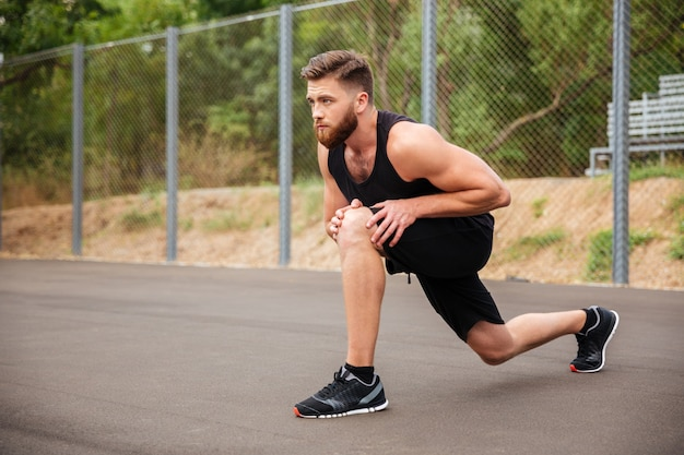 Portrait of a bearded young sports man stretching legs outside